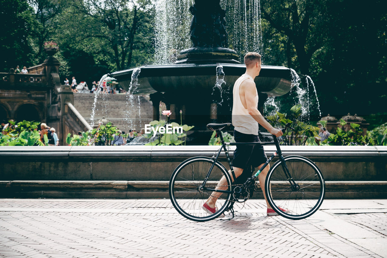 MAN WITH BICYCLE ON TREE BY WATER