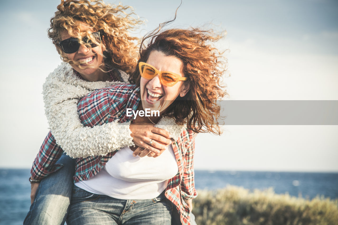 emotion, togetherness, smiling, leisure activity, two people, young adult, land, glasses, lifestyles, casual clothing, happiness, sea, adult, nature, real people, sky, young women, water, men, couple - relationship, positive emotion, outdoors, horizon over water