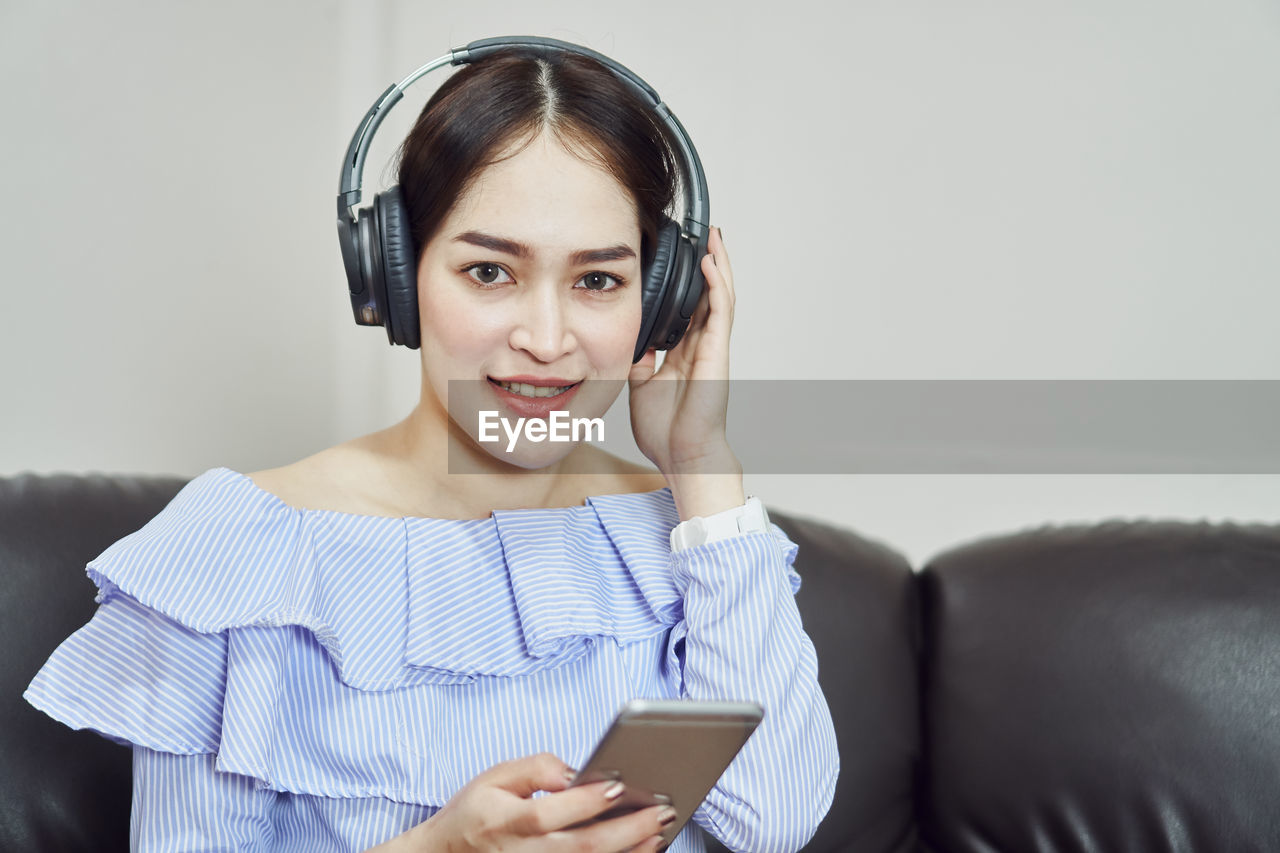 Portrait Of Young Woman Holding Mobile Phone While Listening To Music At Home