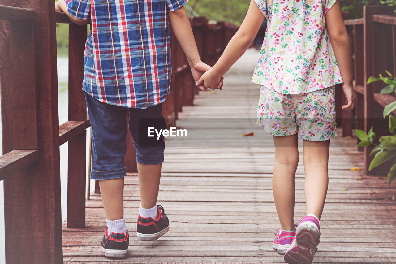 Low section of siblings holding hands while walking on footbridge