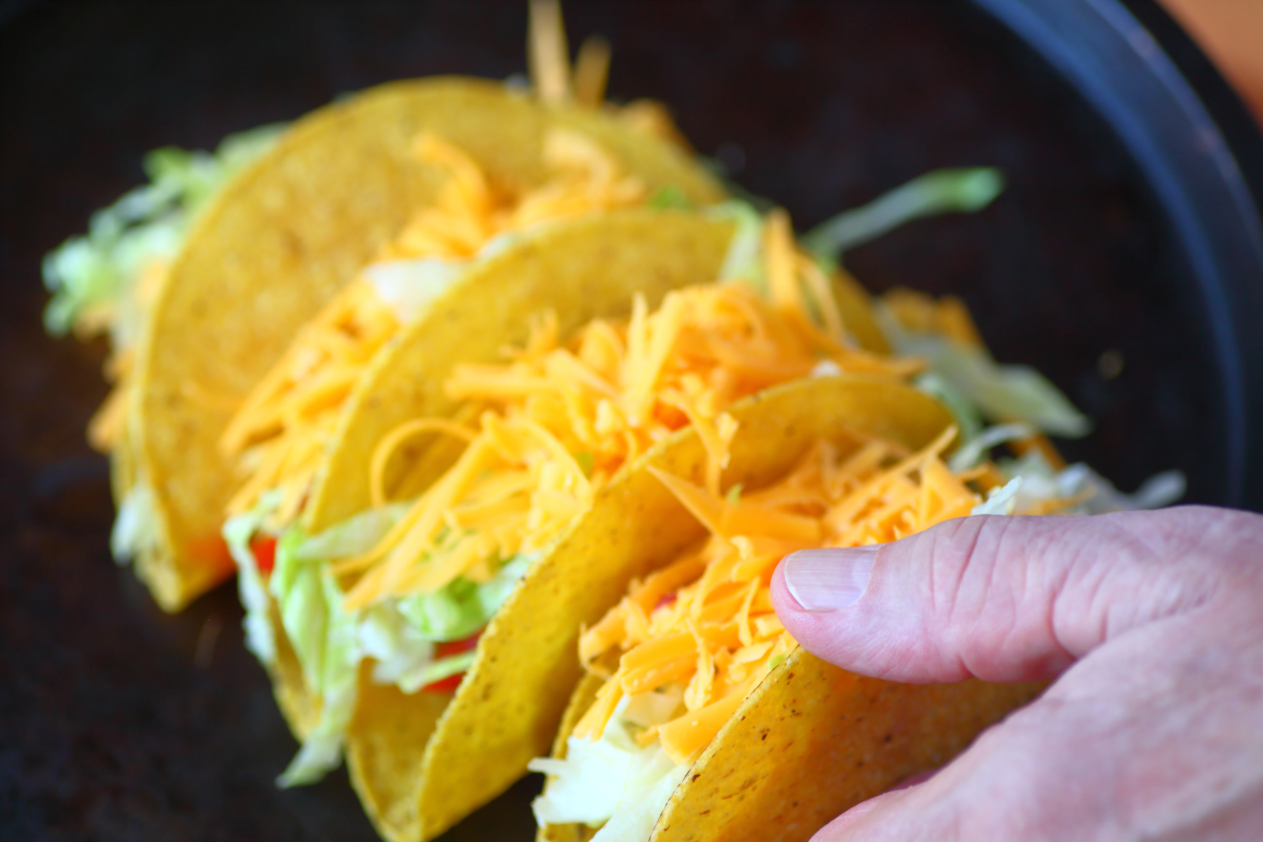 Cropped hand of person holding tacos