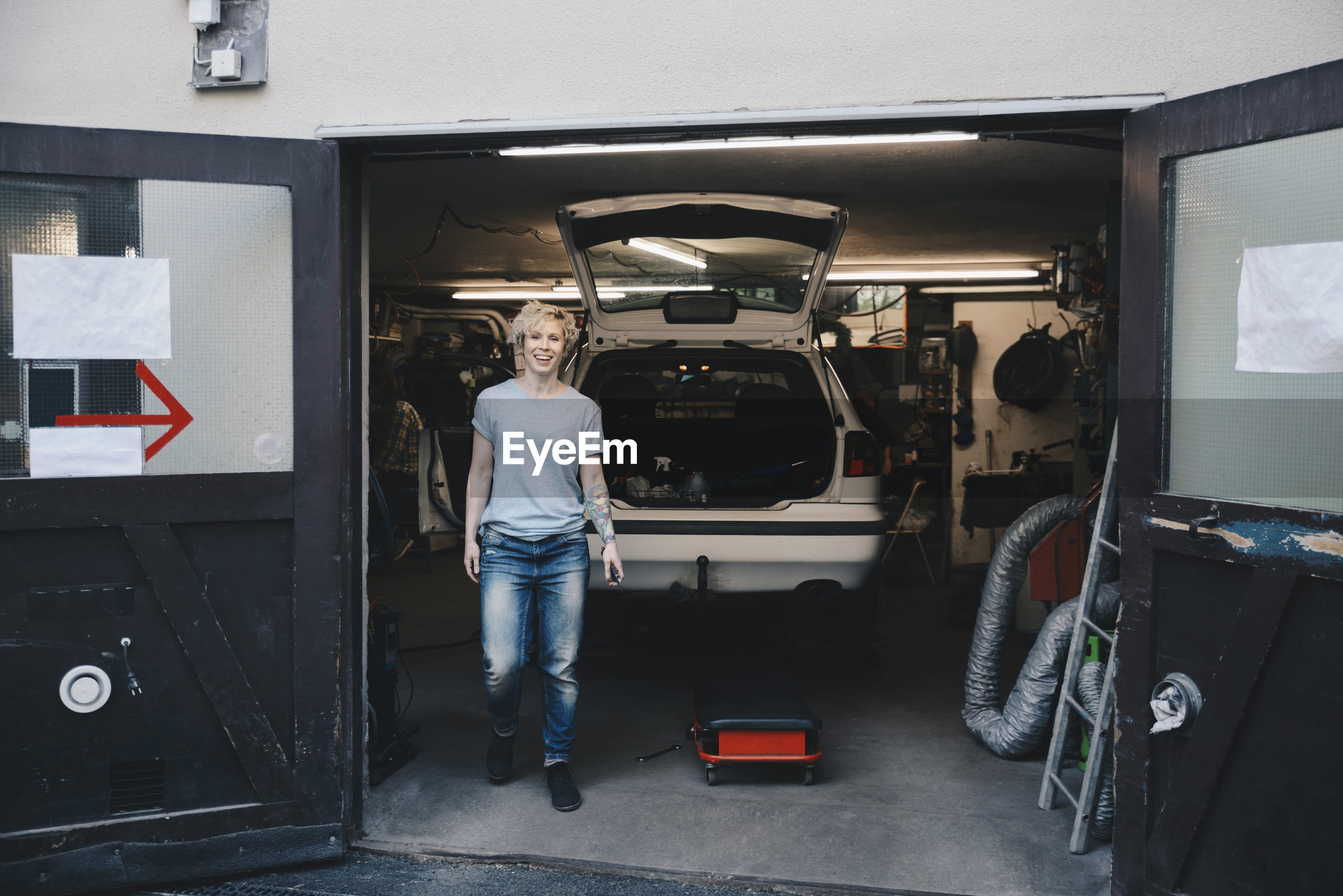 FULL LENGTH PORTRAIT OF WOMAN STANDING BY CAR