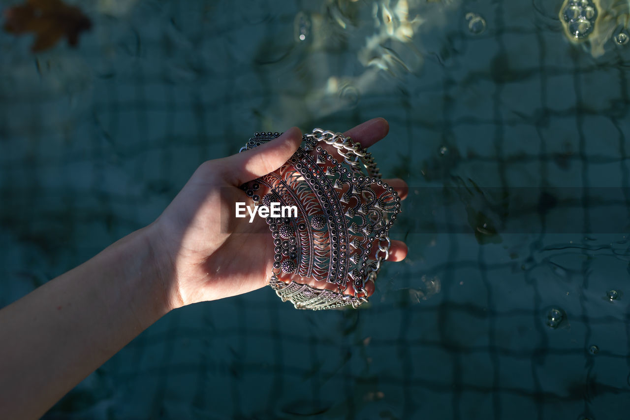 Close-up of hand holding jewelry over swimming pool