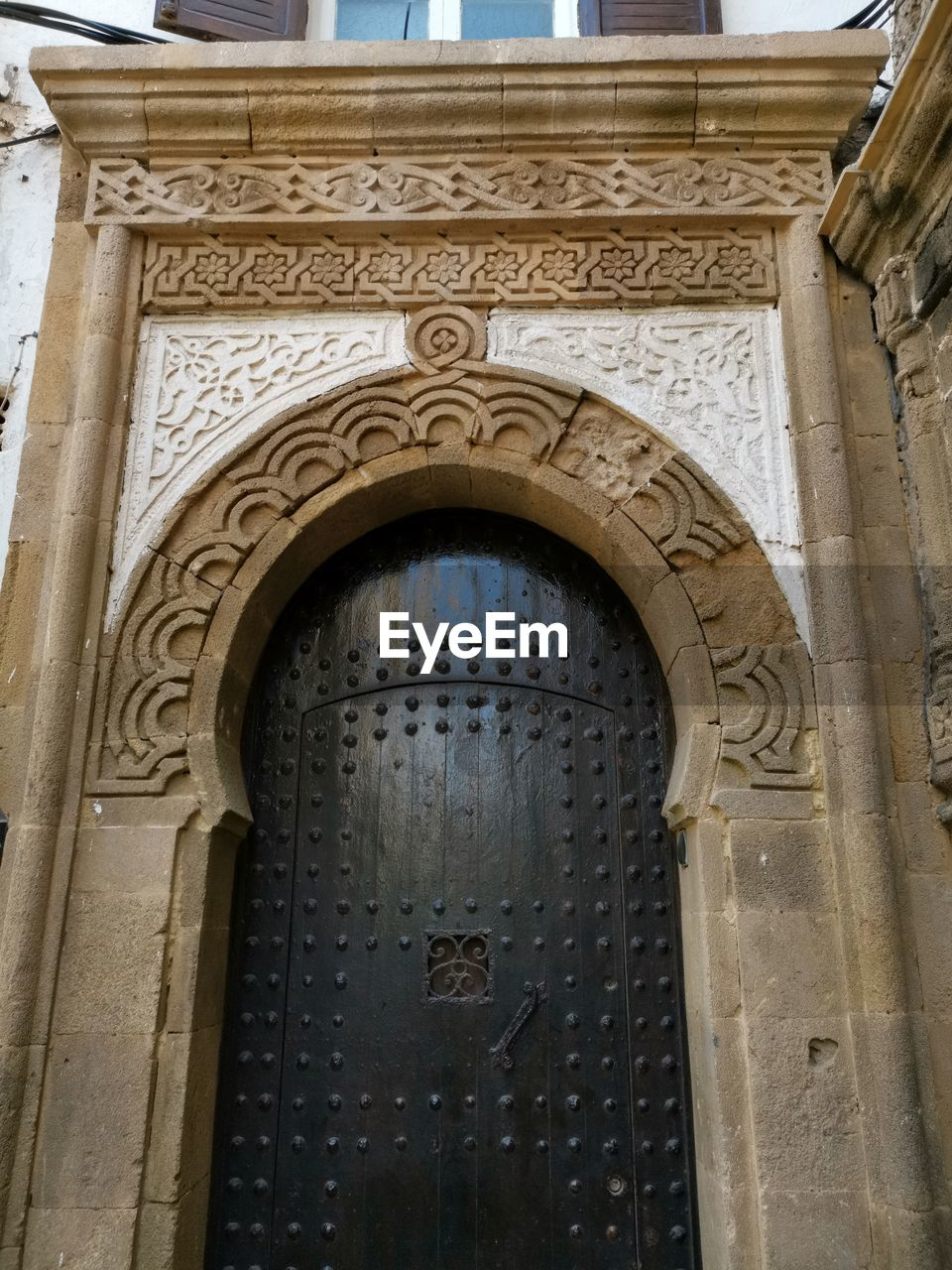 architecture, built structure, arch, building exterior, day, history, low angle view, building, the past, no people, entrance, text, travel destinations, ornate, place of worship, religion, travel, door, outdoors, old, bas relief