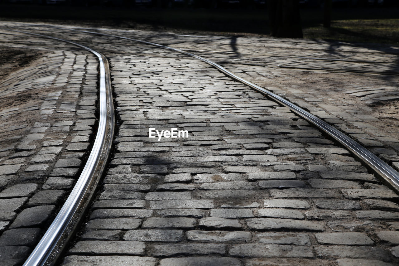 High angle view of railroad tracks on cobbled street