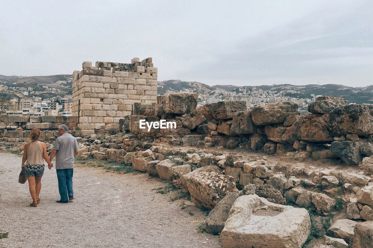 rear view, real people, architecture, history, the past, lifestyles, built structure, ancient, sky, men, tourism, people, adult, travel, women, leisure activity, day, travel destinations, two people, nature, ancient civilization, outdoors, couple - relationship, positive emotion, archaeology, stone wall