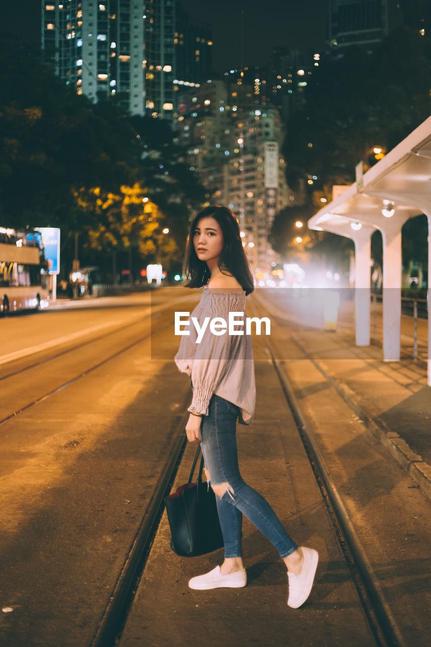 Beautiful woman standing on street at night