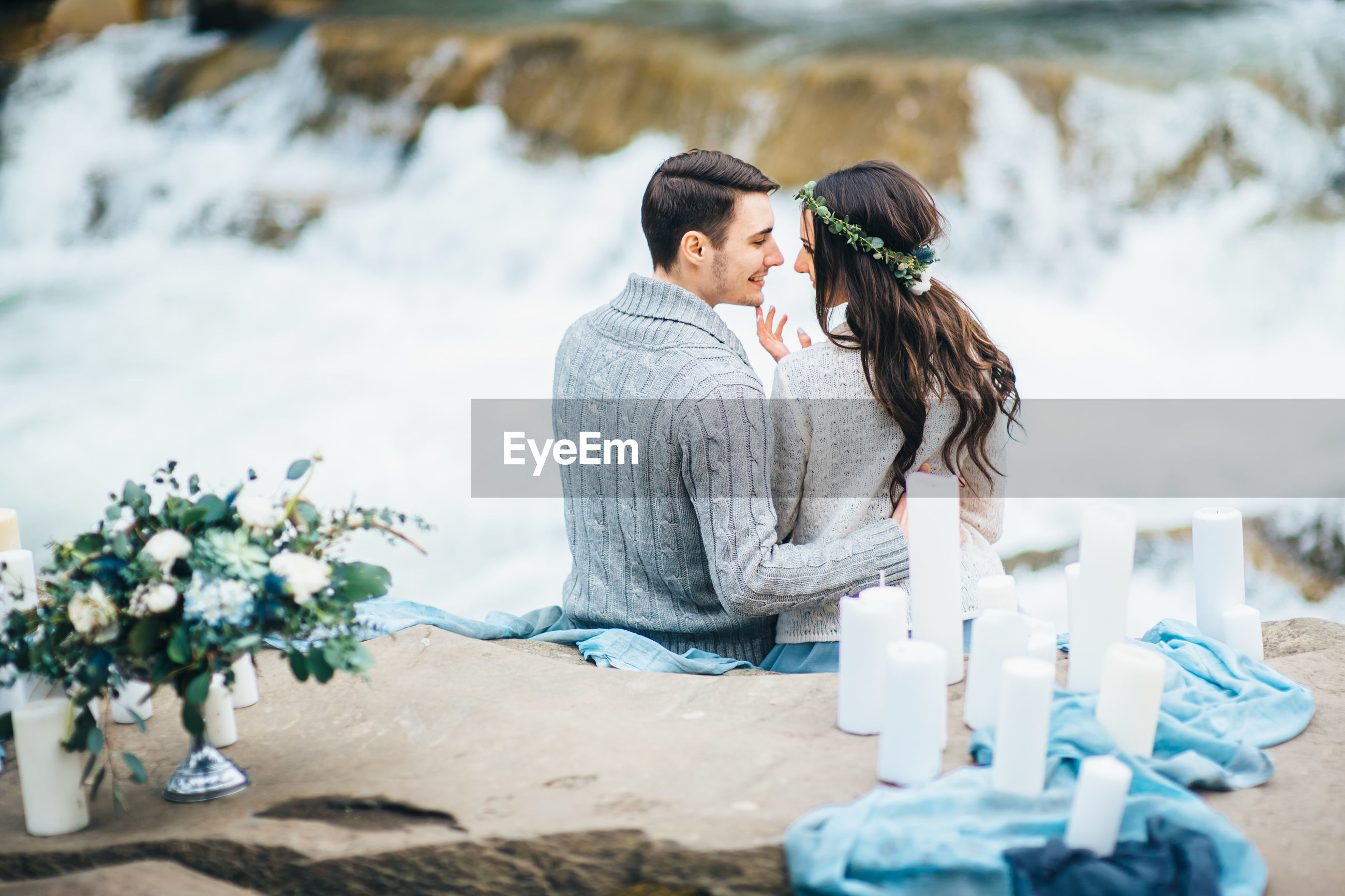 REAR VIEW OF COUPLE SITTING ON WATER