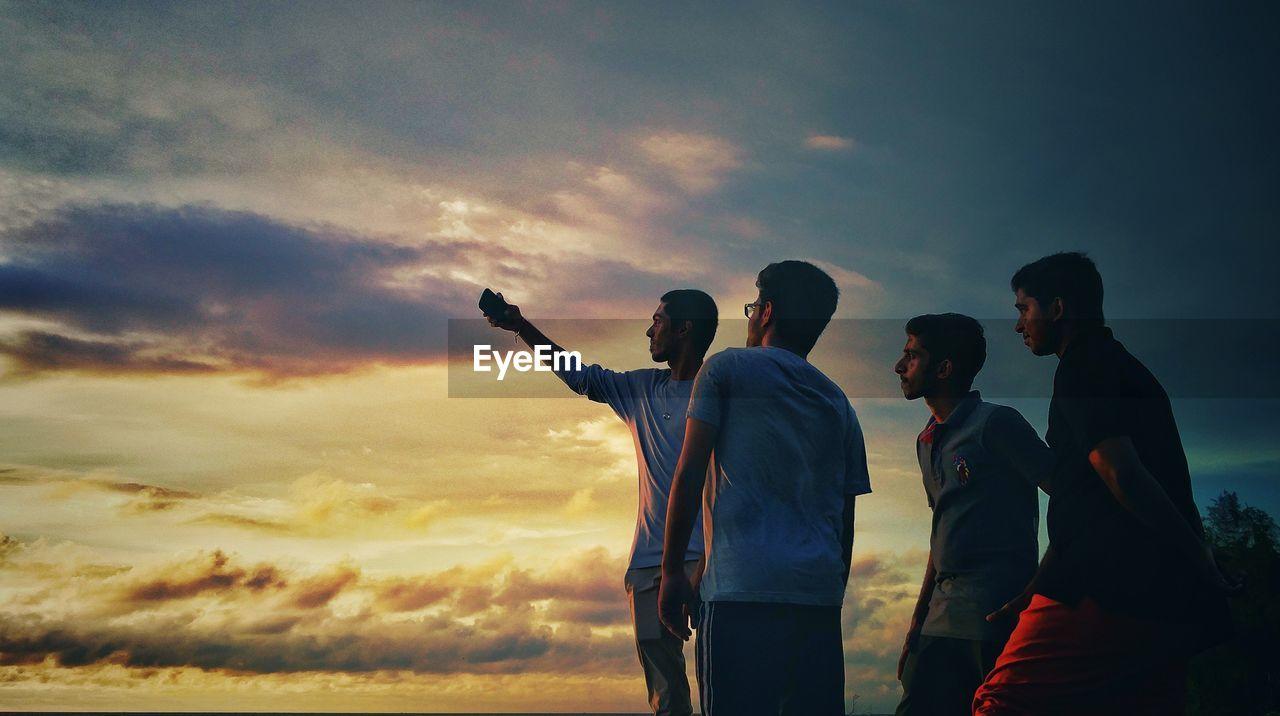 Friends taking selfie through mobile phone against sky