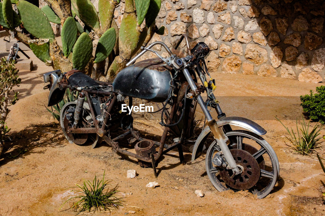 transportation, mode of transportation, motorcycle, day, nature, stationary, land vehicle, no people, outdoors, tree, travel, rock, land, wall - building feature, wall, rock - object, solid, wheel, architecture, arid climate