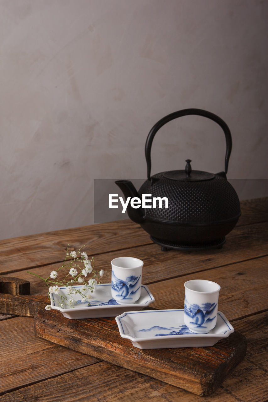 HIGH ANGLE VIEW OF TEA CUP ON TABLE AGAINST WALL