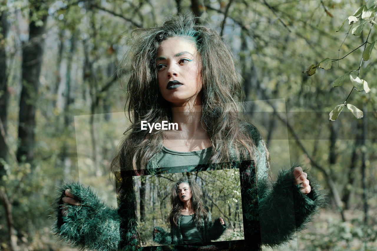 Serious Young Woman With Spooky Make-Up Holding Picture Frame While Standing In Forest