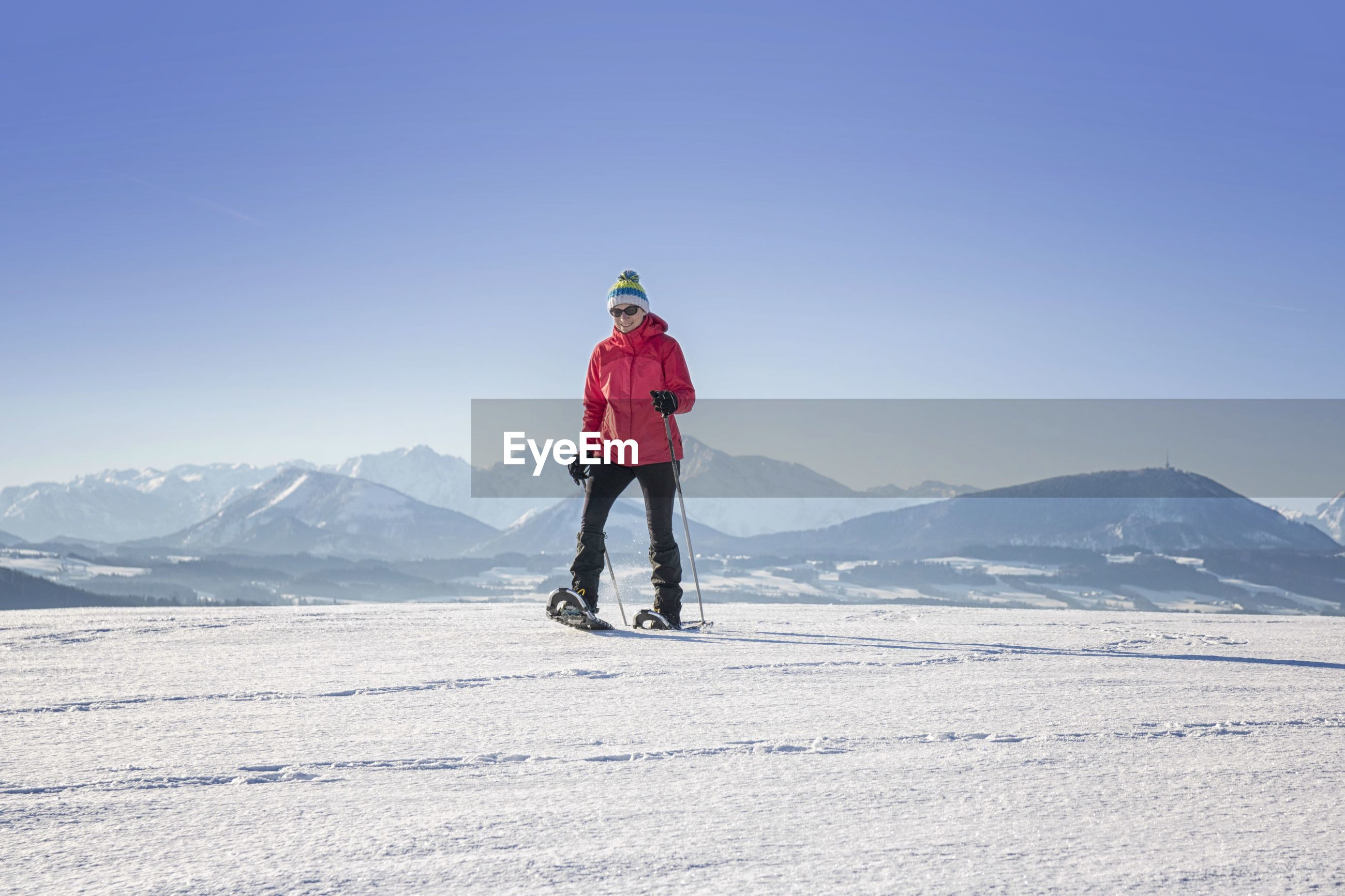 Woman snowboarding on land against clear blue sky