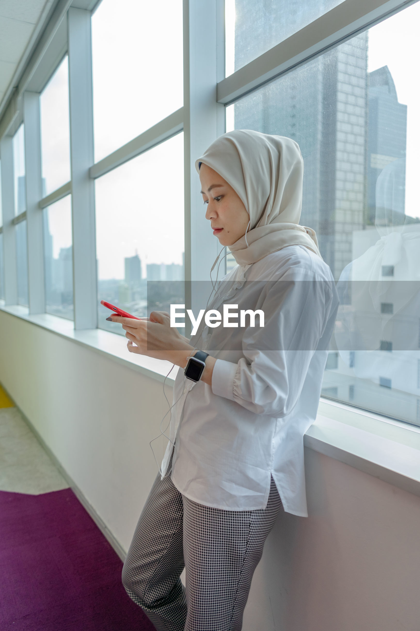SIDE VIEW OF WOMAN USING SMART PHONE