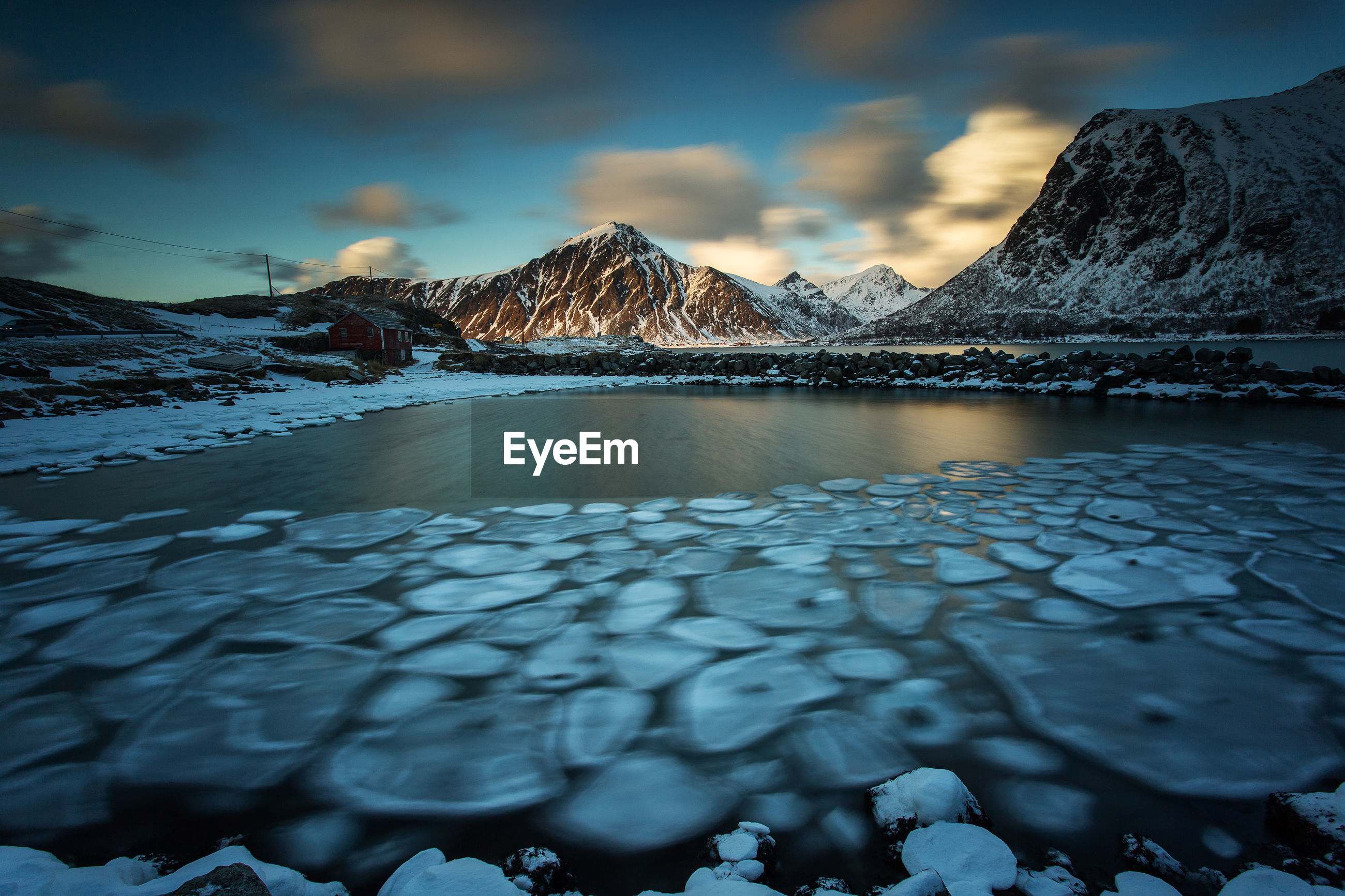 FROZEN LAKE BY SNOWCAPPED MOUNTAIN AGAINST SKY