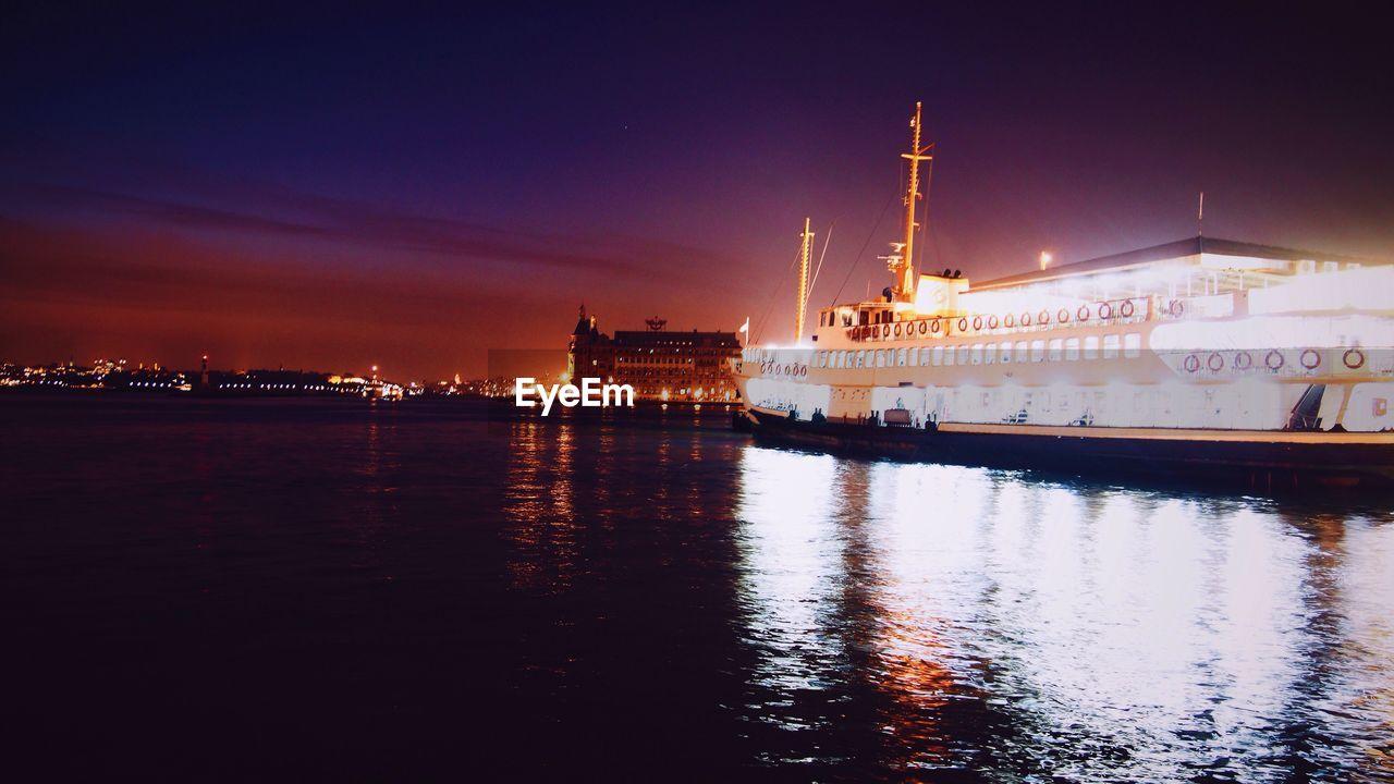 Illuminated Ship On Lake Against Sky At Night