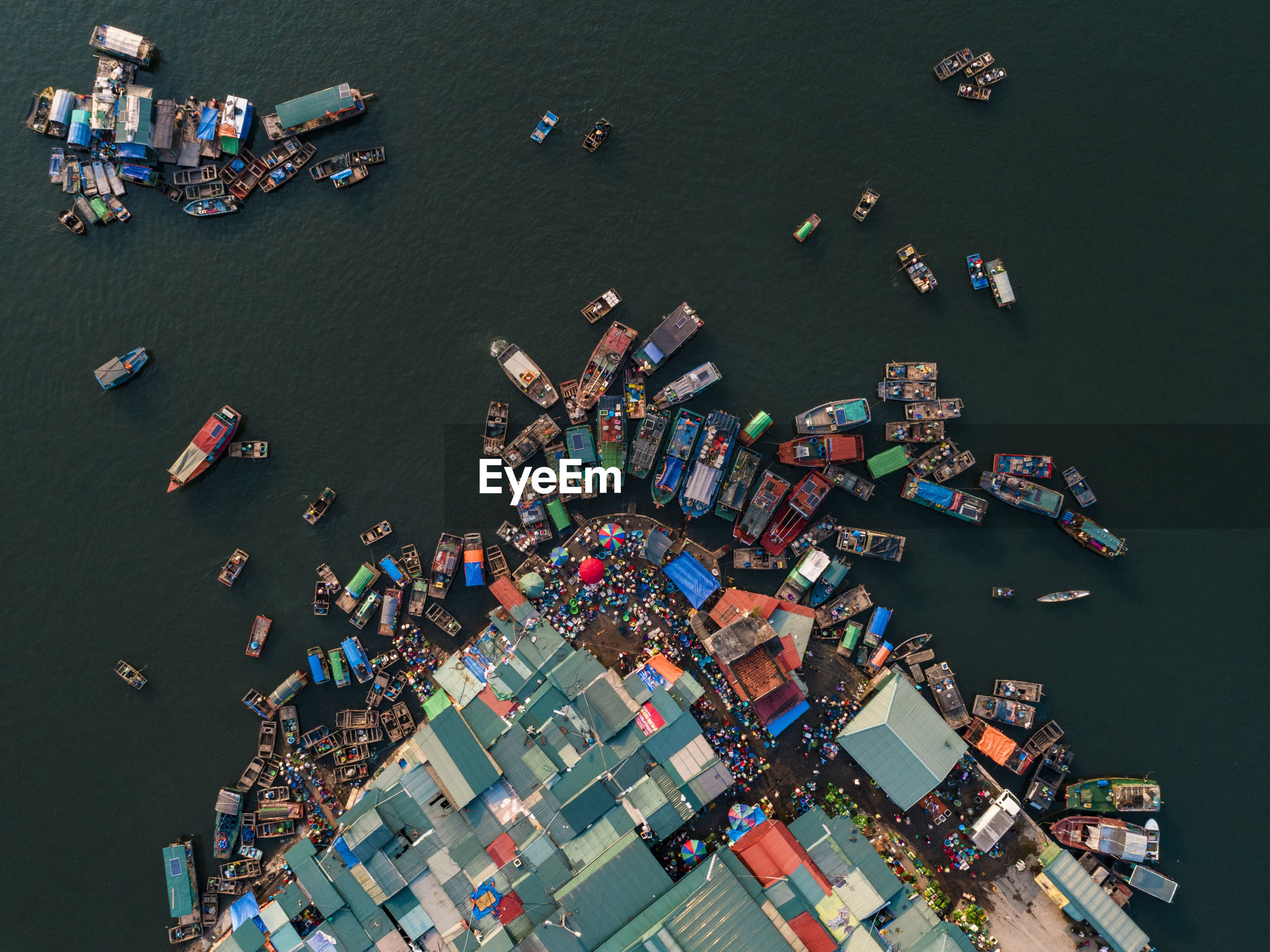 Aerial view of boats moored at harbor in sea
