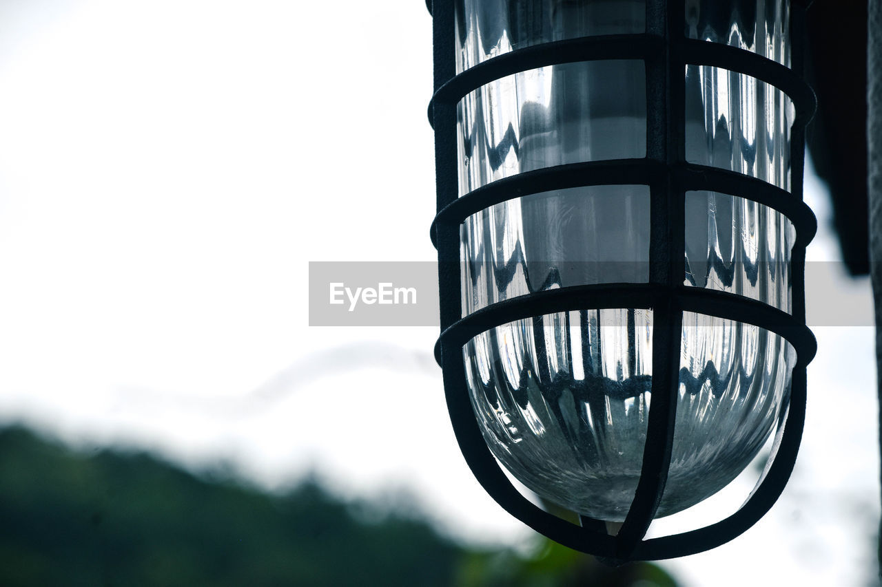 close-up, focus on foreground, sky, no people, low angle view, day, glass - material, nature, lighting equipment, transparent, outdoors, clear sky, pattern, copy space, shape, design, metal, tree, electricity, built structure, electric lamp