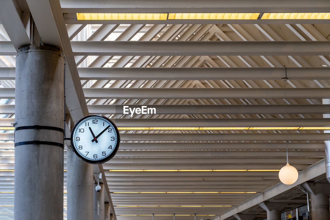 clock, low angle view, architecture, time, ceiling, no people, indoors, built structure, illuminated, lighting equipment, metal, pattern, instrument of time, hanging, clock face, architectural column, number, building, pipe - tube, roof beam