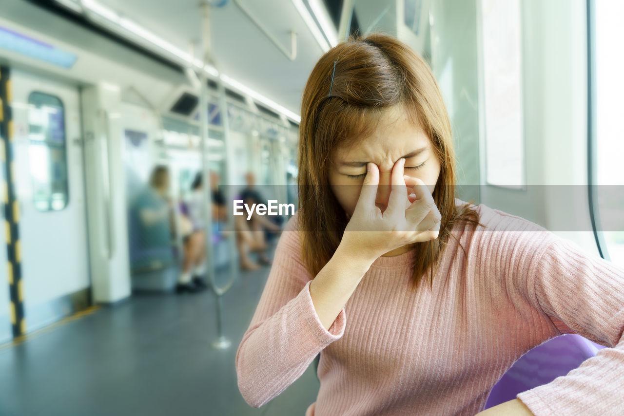 Woman With Headache Sitting In Train