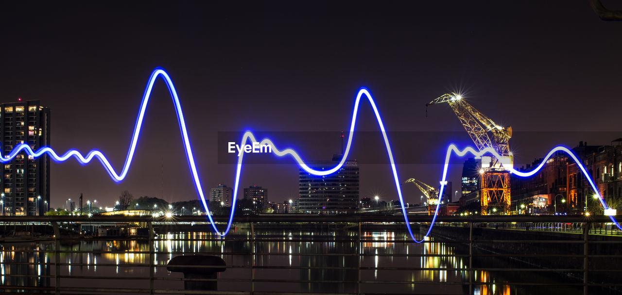 Light painting over railing against buildings in city at night