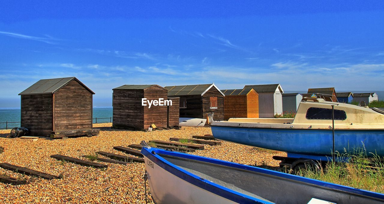 Boats and hut at beach against sky