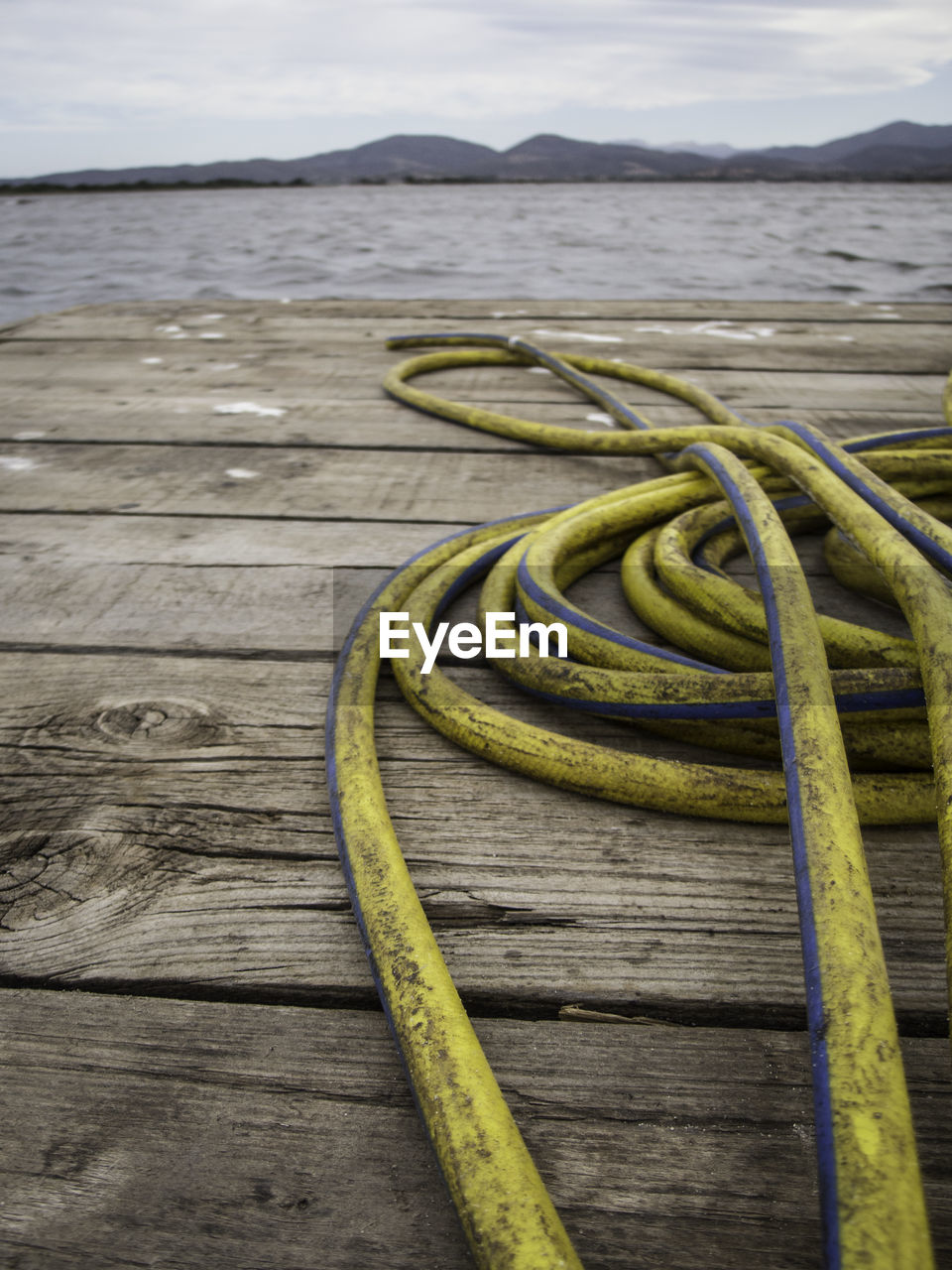 wood - material, no people, yellow, water, close-up, nature, day, rope, table, outdoors, focus on foreground, beauty in nature, metal, land, sea, spiral, connection, boardwalk, wood