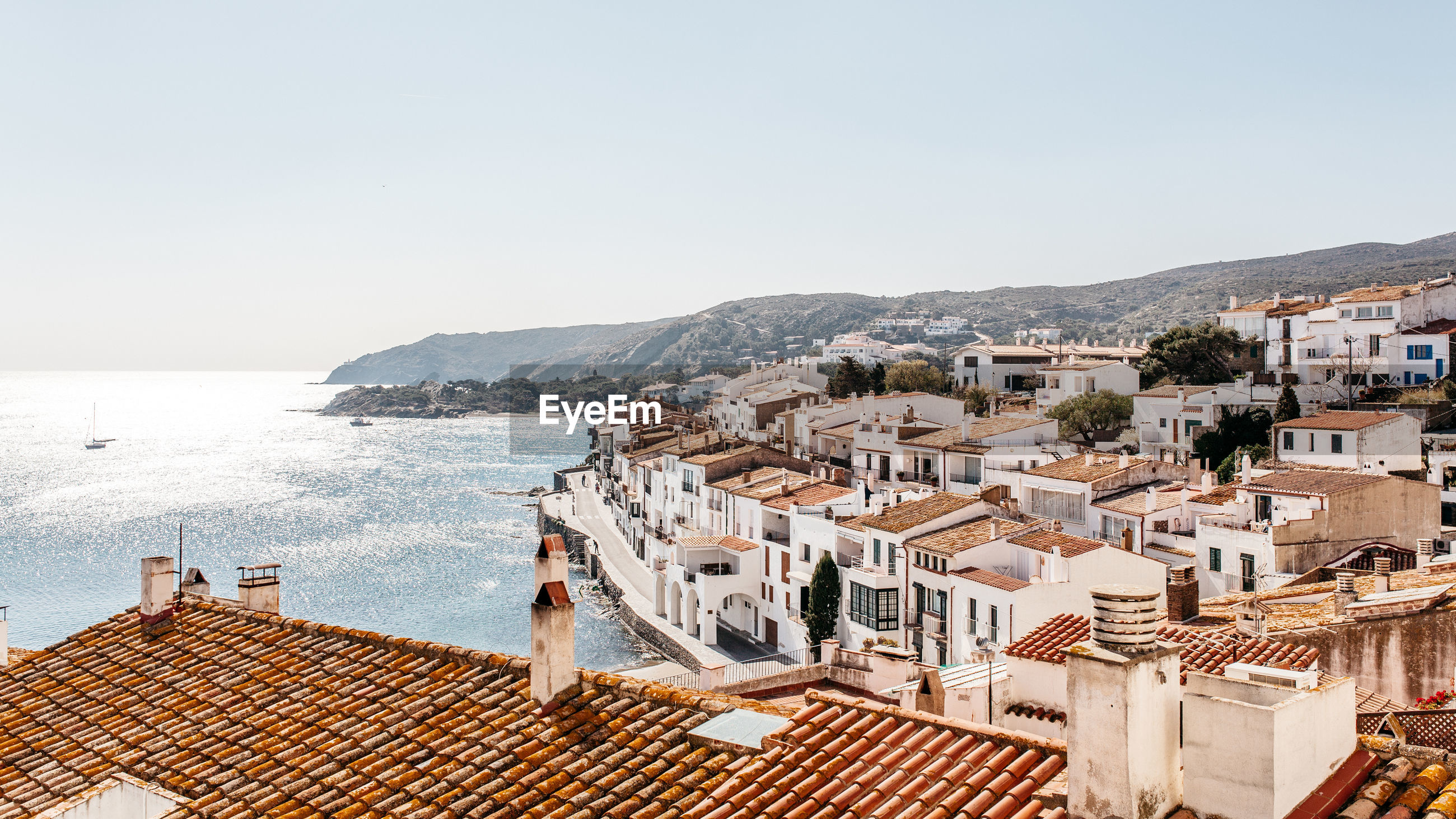 VIEW OF TOWN BY SEA AGAINST CLEAR SKY