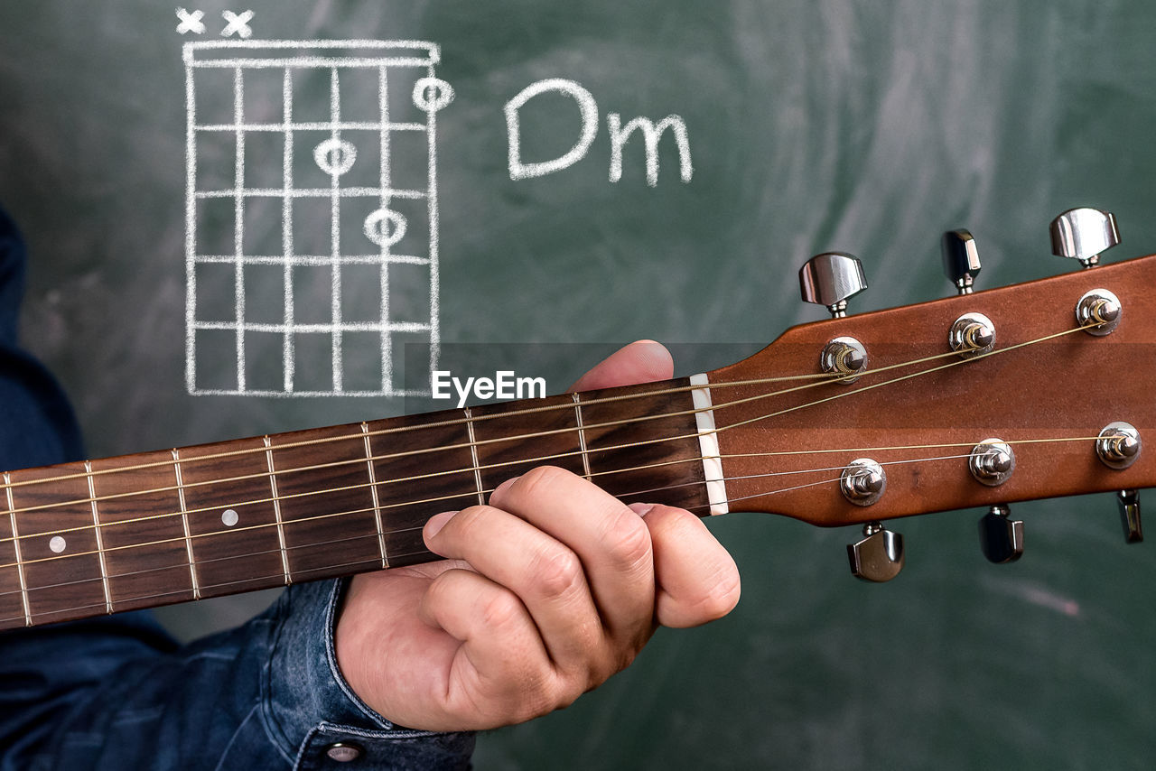 Cropped hand of man playing guitar against blackboard