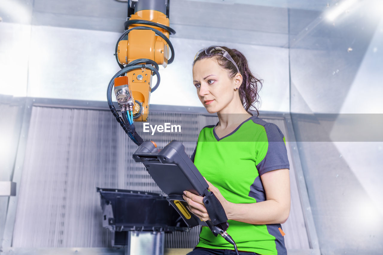 Woman Working On Machinery In Factory