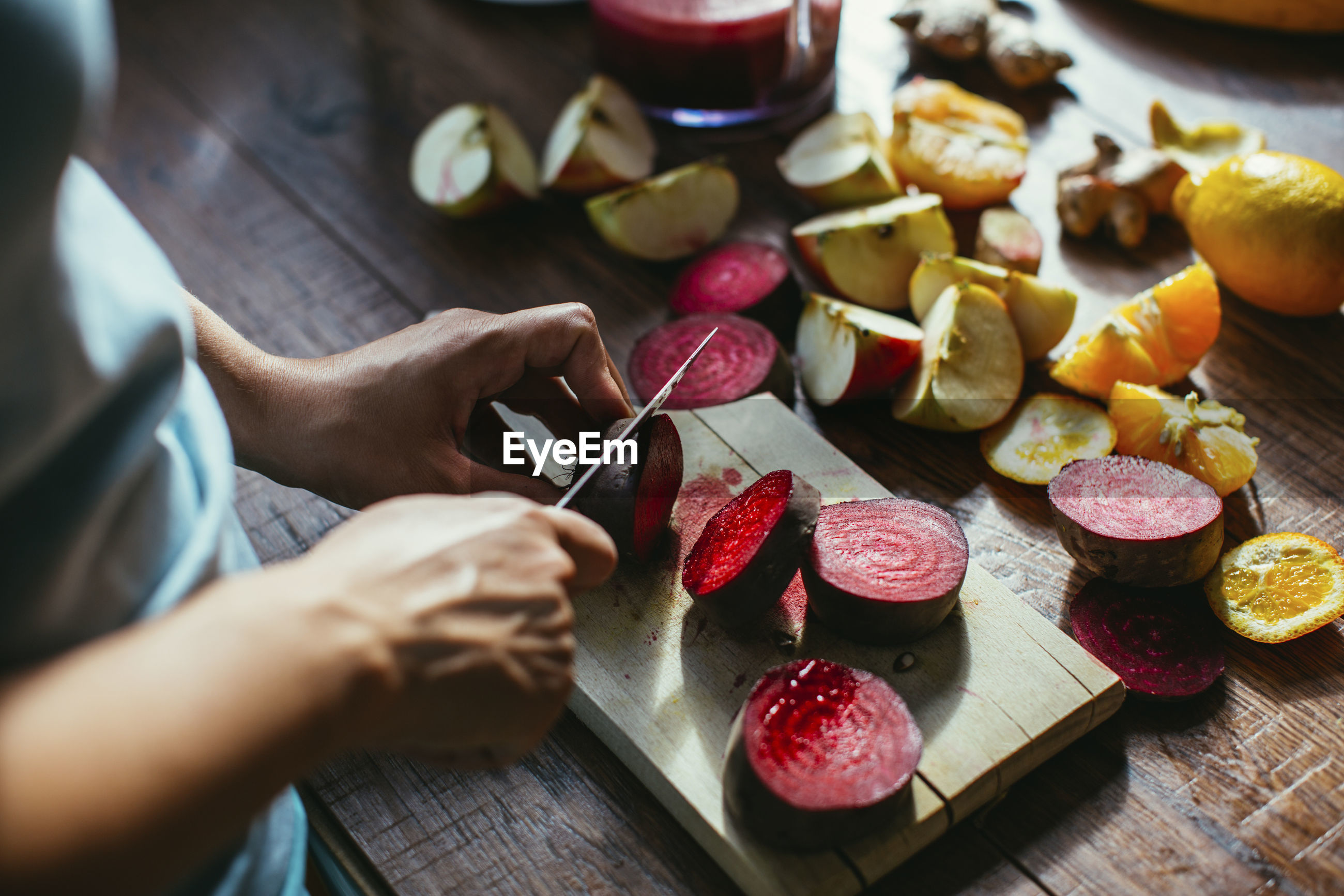HIGH ANGLE VIEW OF HAND HOLDING FRUITS ON TABLE