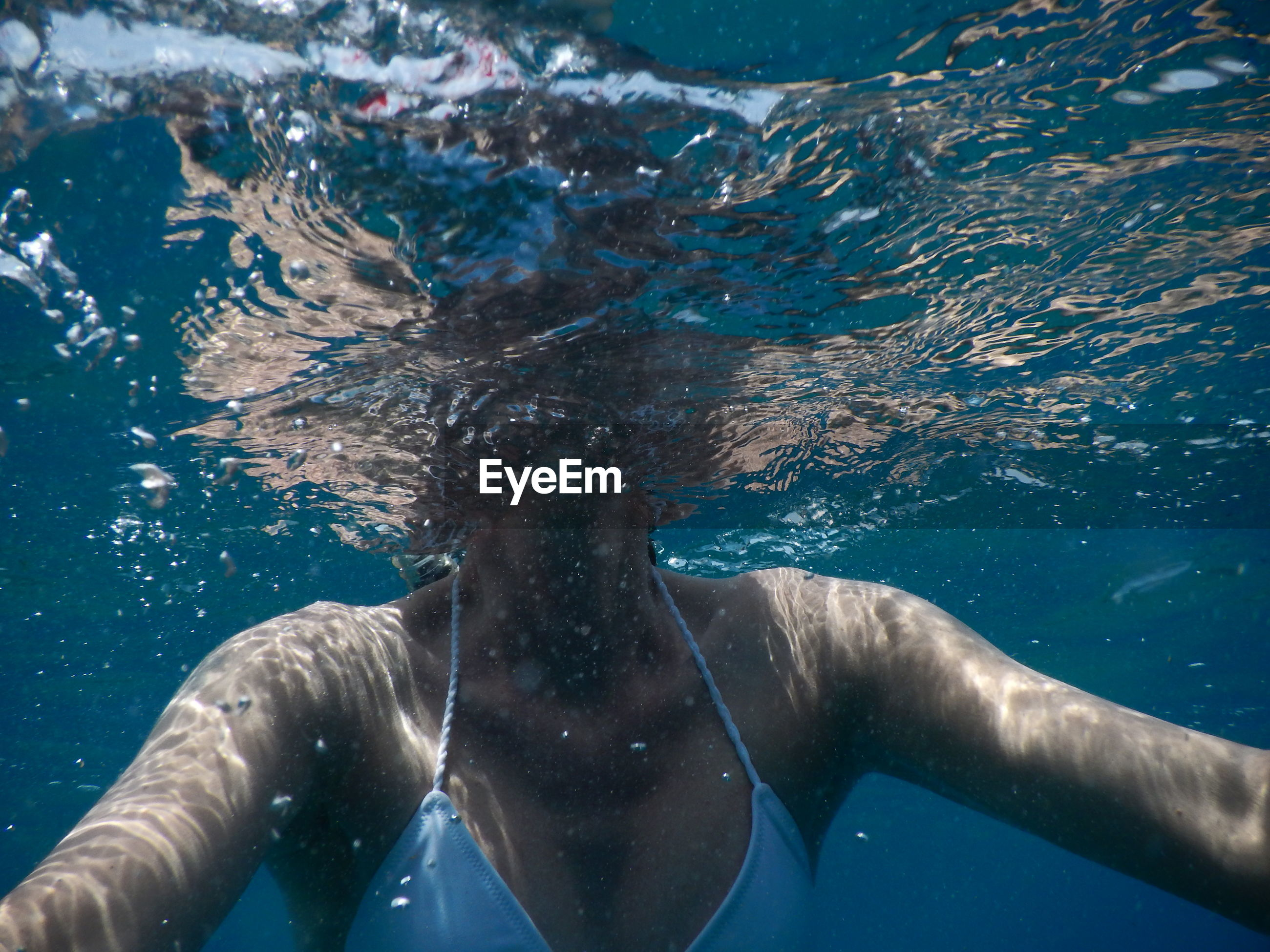 Midsection of woman swimming in sea