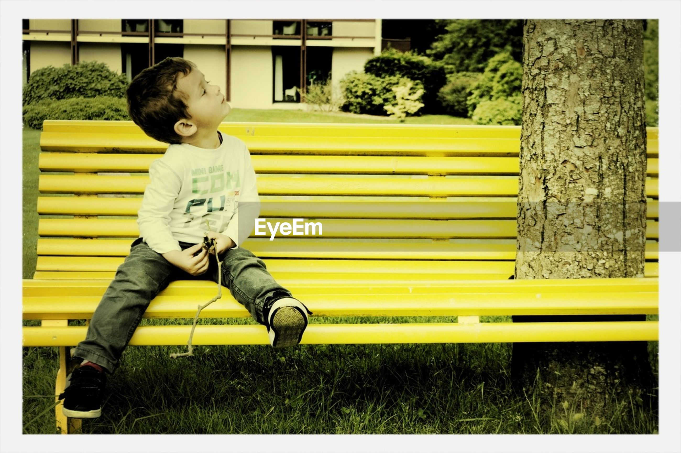 transfer print, auto post production filter, childhood, yellow, full length, elementary age, boys, casual clothing, day, person, lifestyles, outdoors, park - man made space, sitting, railing, toy, playground, front view