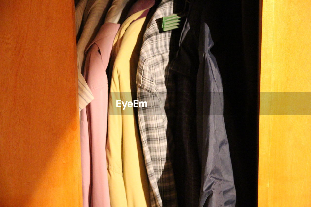 clothing, choice, variation, indoors, hanging, closet, no people, multi colored, textile, retail, store, in a row, shopping, fashion, rack, coathanger, still life, large group of objects, side by side, yellow, retail display, menswear, consumerism