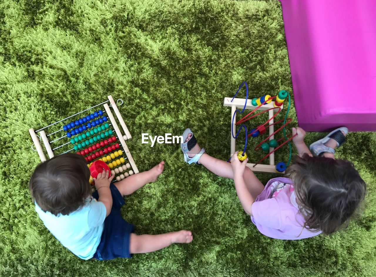 High Angle View Of Siblings Playing With Toys On Carpet At Home