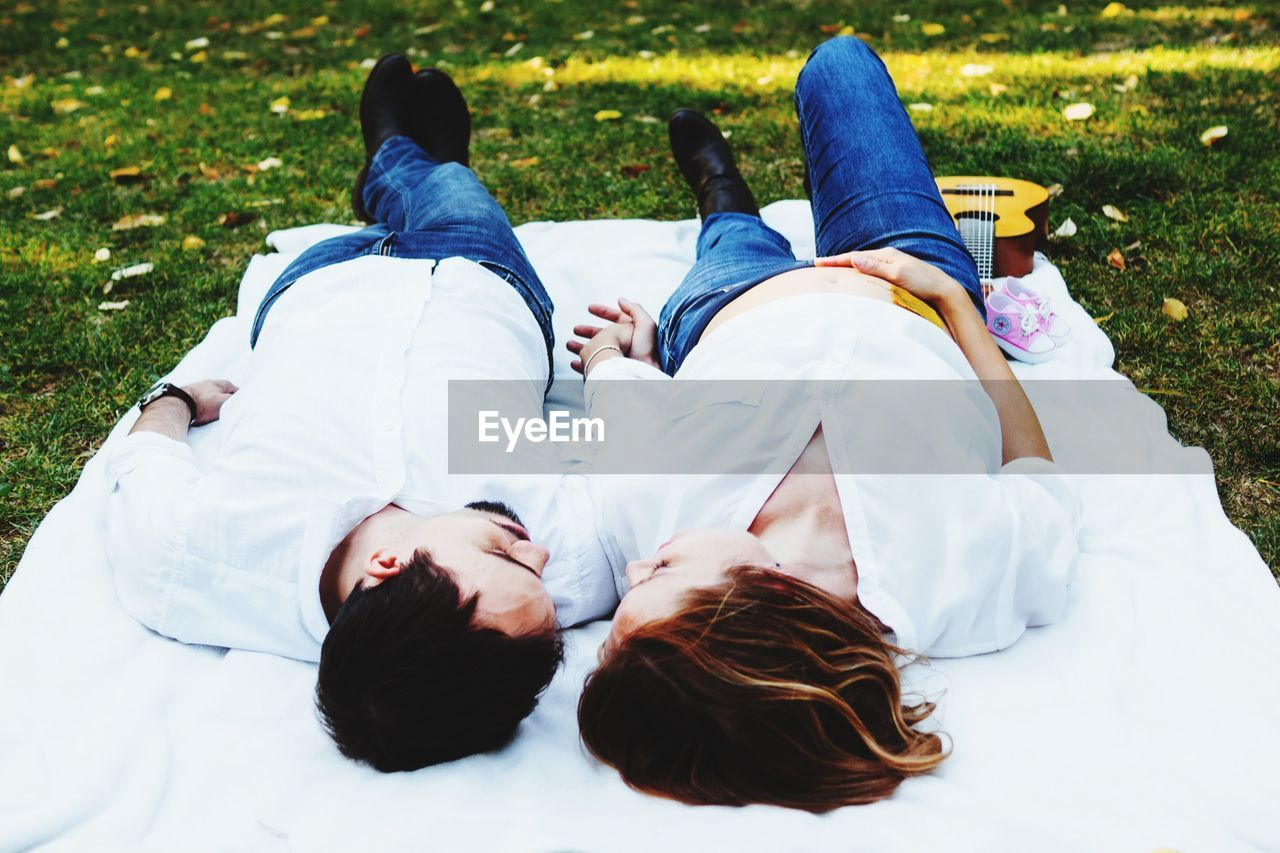 Man And Woman Lying On Picnic Blanket