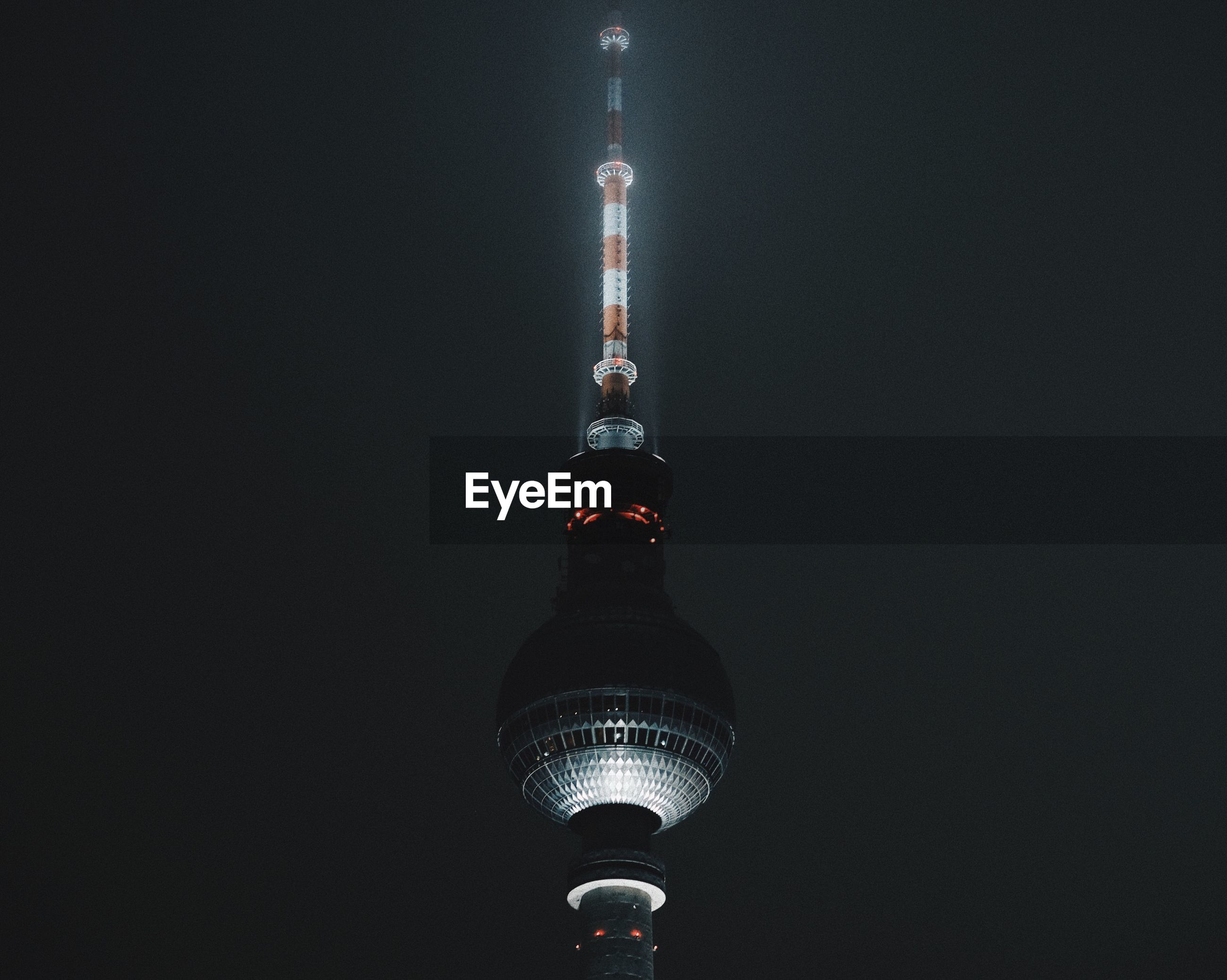 Illuminated fernsehturm against sky at night