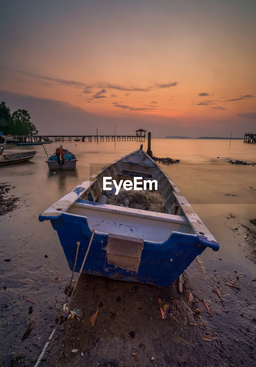 water, sunset, nautical vessel, sky, transportation, mode of transportation, land, sea, beach, moored, scenics - nature, beauty in nature, nature, tranquility, cloud - sky, tranquil scene, no people, sand, orange color, outdoors, fishing boat, rowboat
