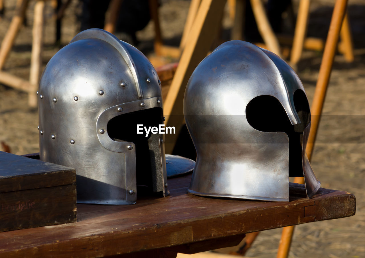 Close-up of old helmets on table outdoors