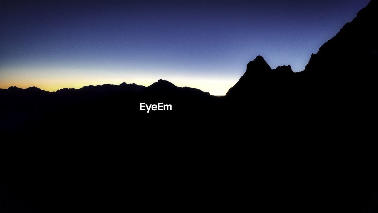 silhouette, sky, mountain, copy space, beauty in nature, scenics - nature, tranquility, tranquil scene, sunset, clear sky, mountain range, nature, no people, dark, dusk, non-urban scene, idyllic, landscape, environment, outdoors, mountain peak