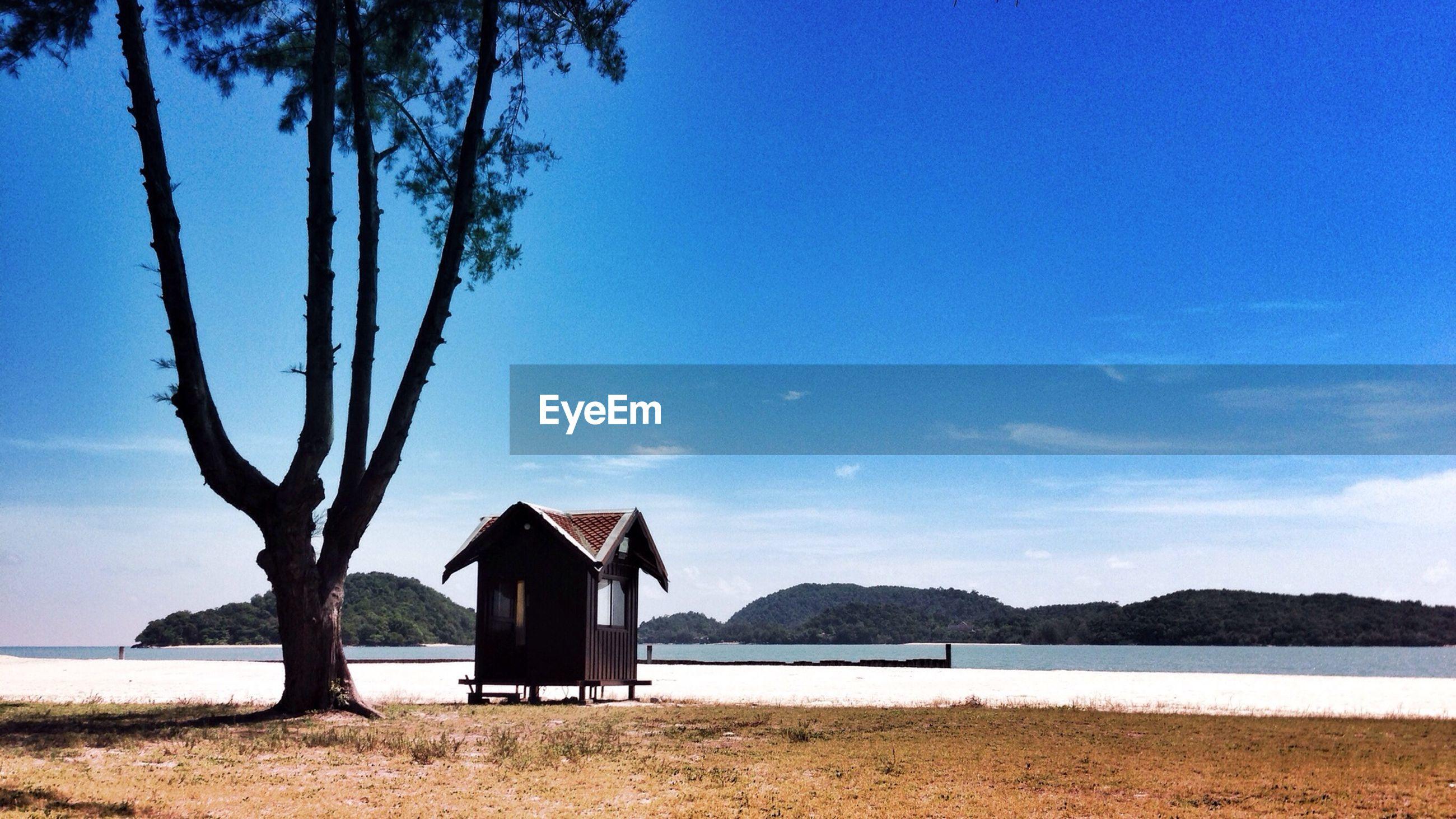 Built structure on calm beach against blue sky