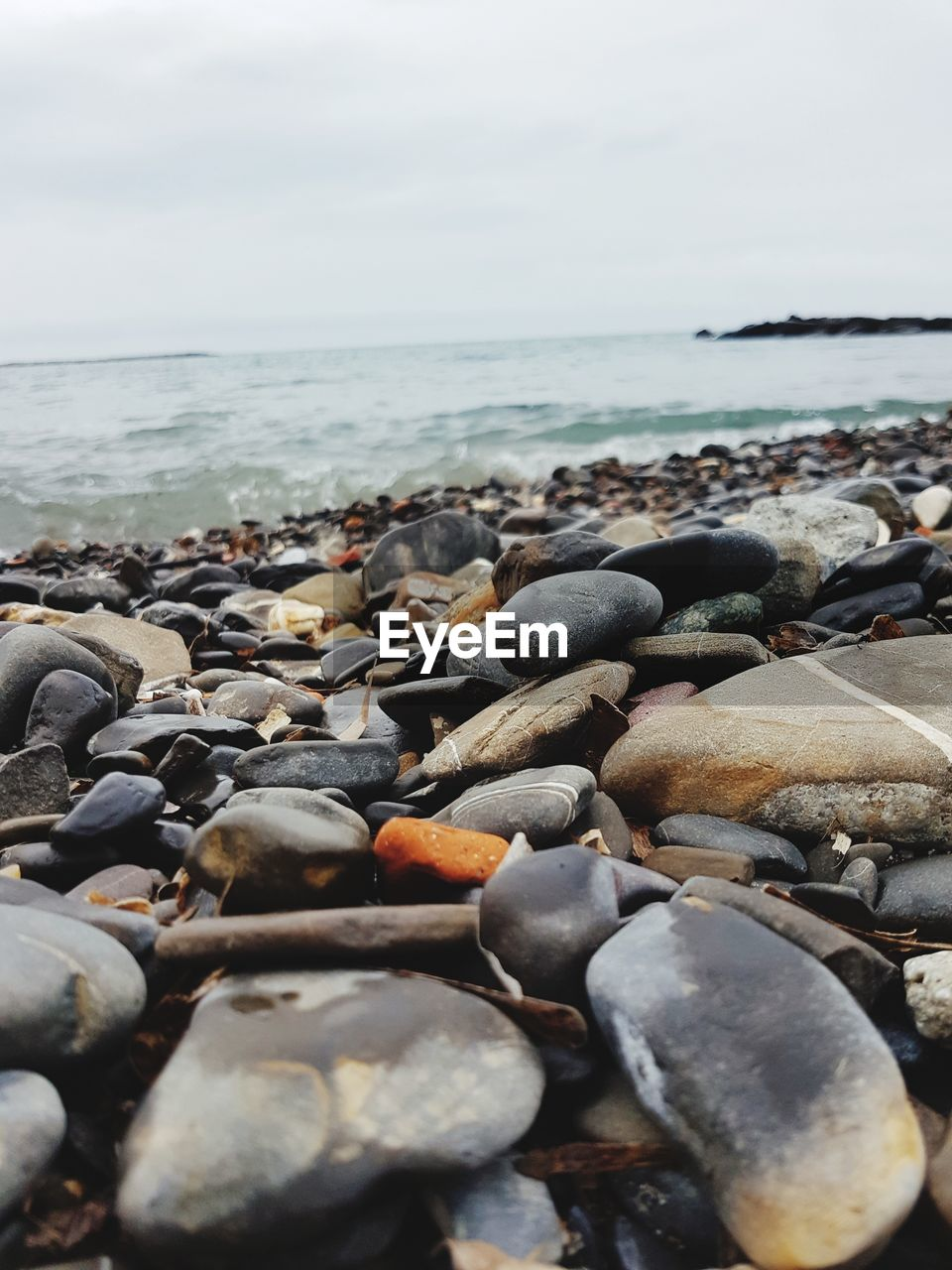 sea, water, beach, land, rock, solid, beauty in nature, sky, scenics - nature, stone, tranquility, nature, horizon over water, day, stone - object, rock - object, pebble, horizon, tranquil scene, no people, surface level, outdoors, pollution, rocky coastline