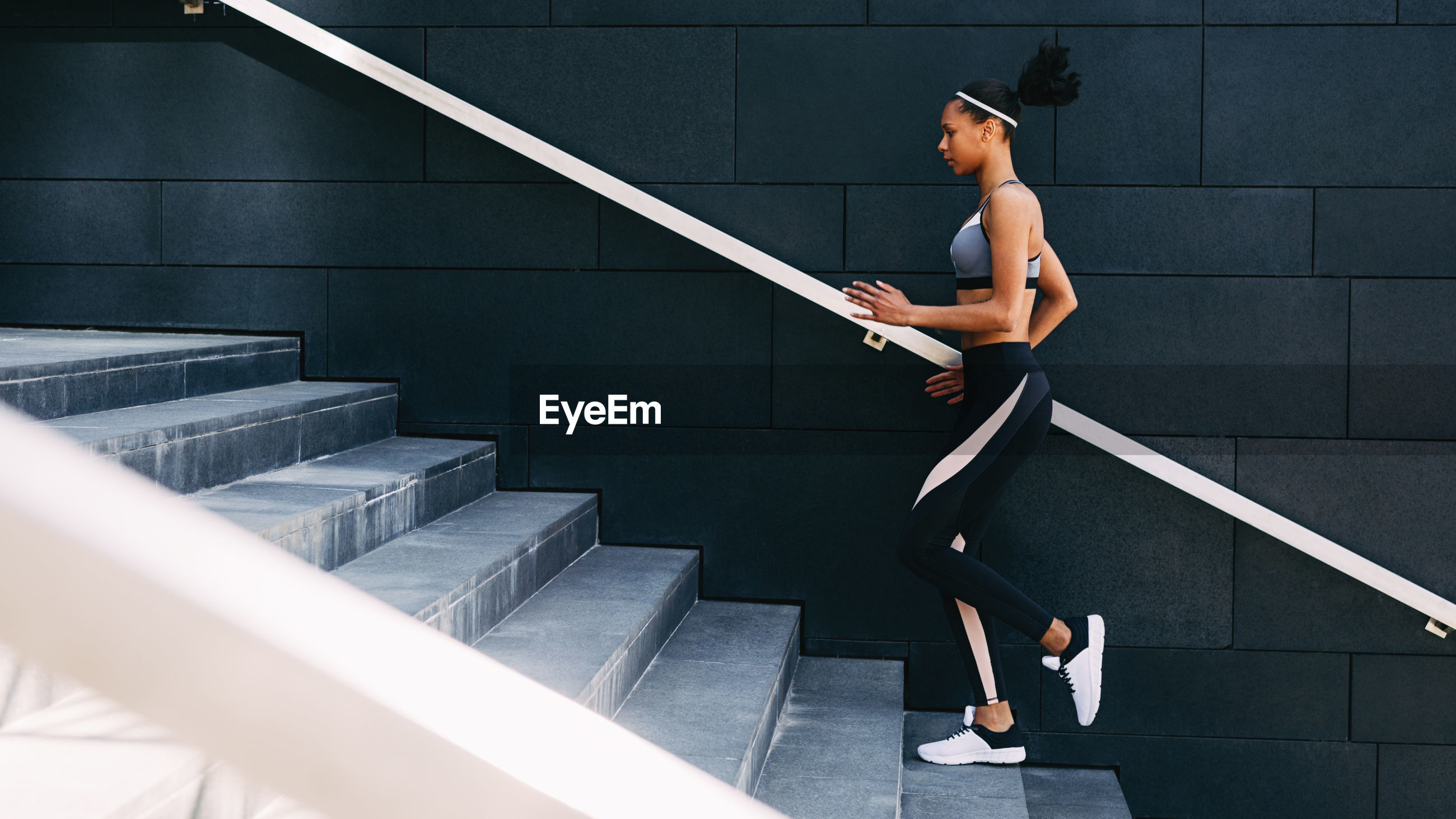 Full length of woman climbing steps against wall