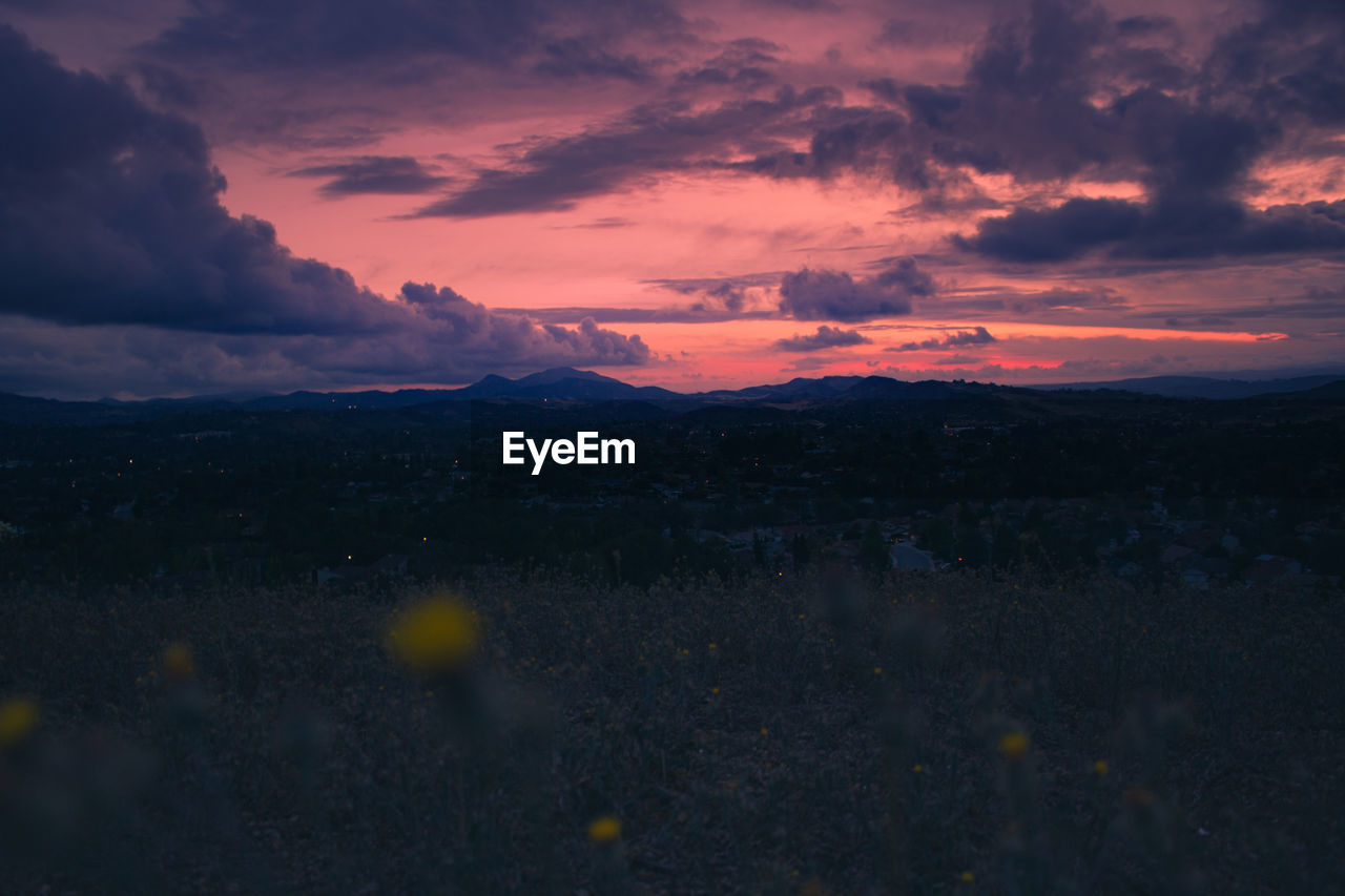 Scenic view of landscape against cloudy, pink sky at dusk