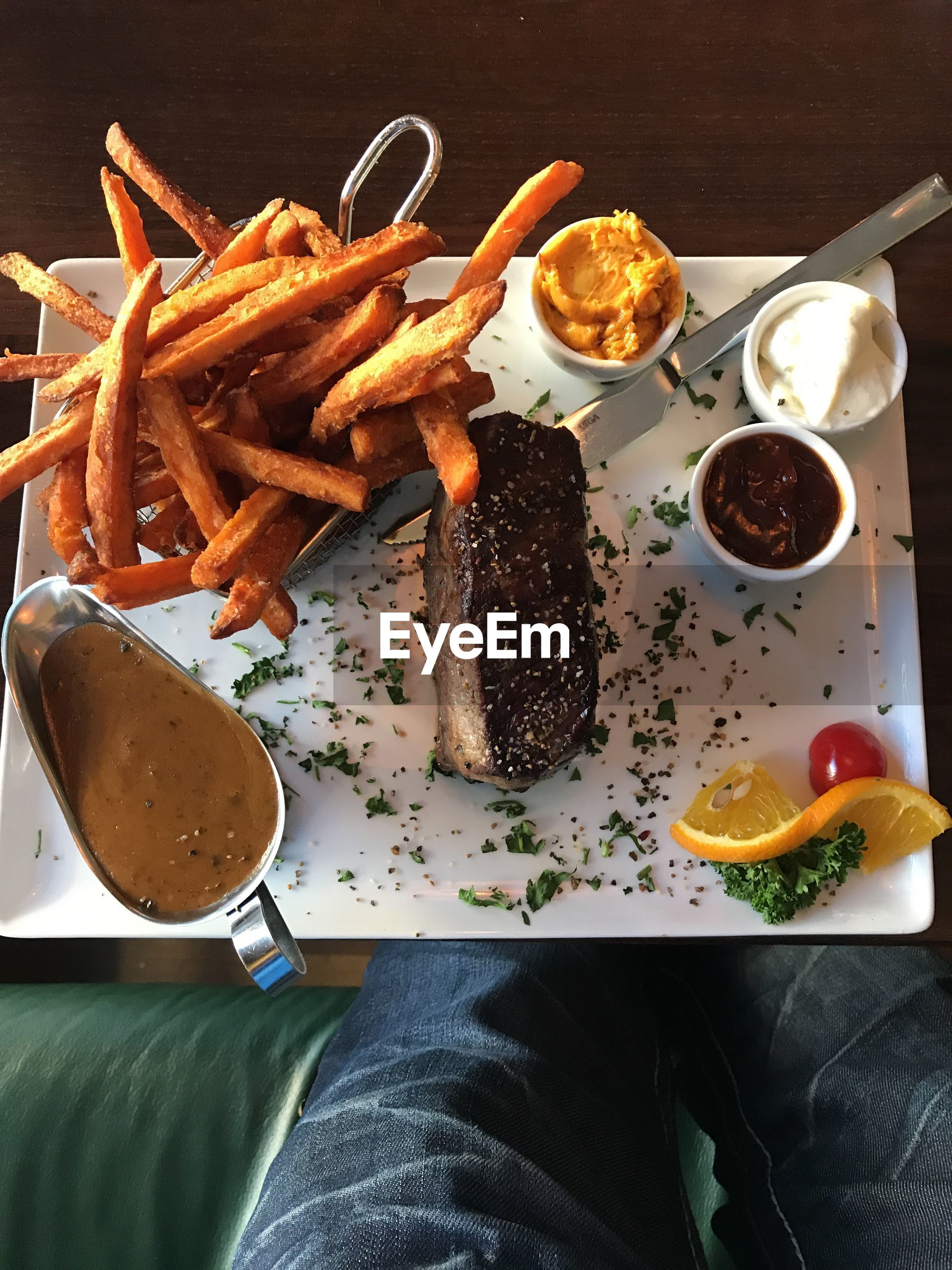 High angle view of meat with french fries and dips on table