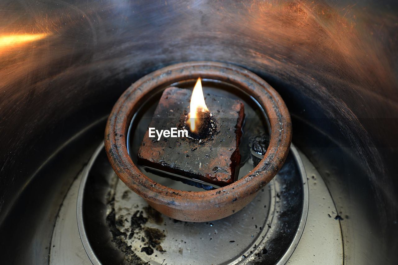 High Angle View Of Burning Diya In Container