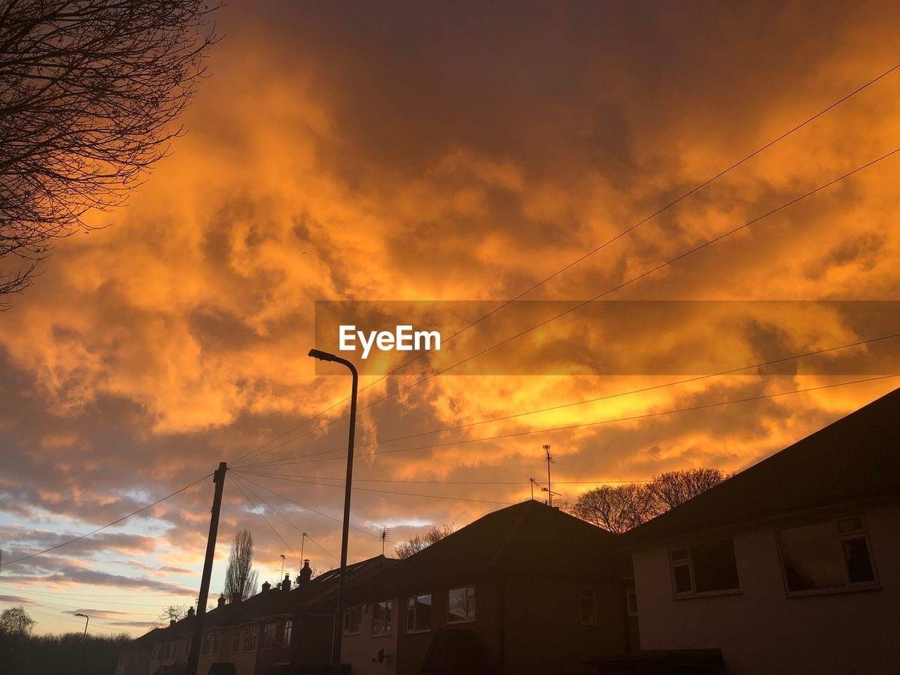 architecture, cloud - sky, sunset, built structure, building exterior, sky, building, silhouette, no people, orange color, nature, street light, beauty in nature, street, house, dramatic sky, residential district, low angle view, outdoors