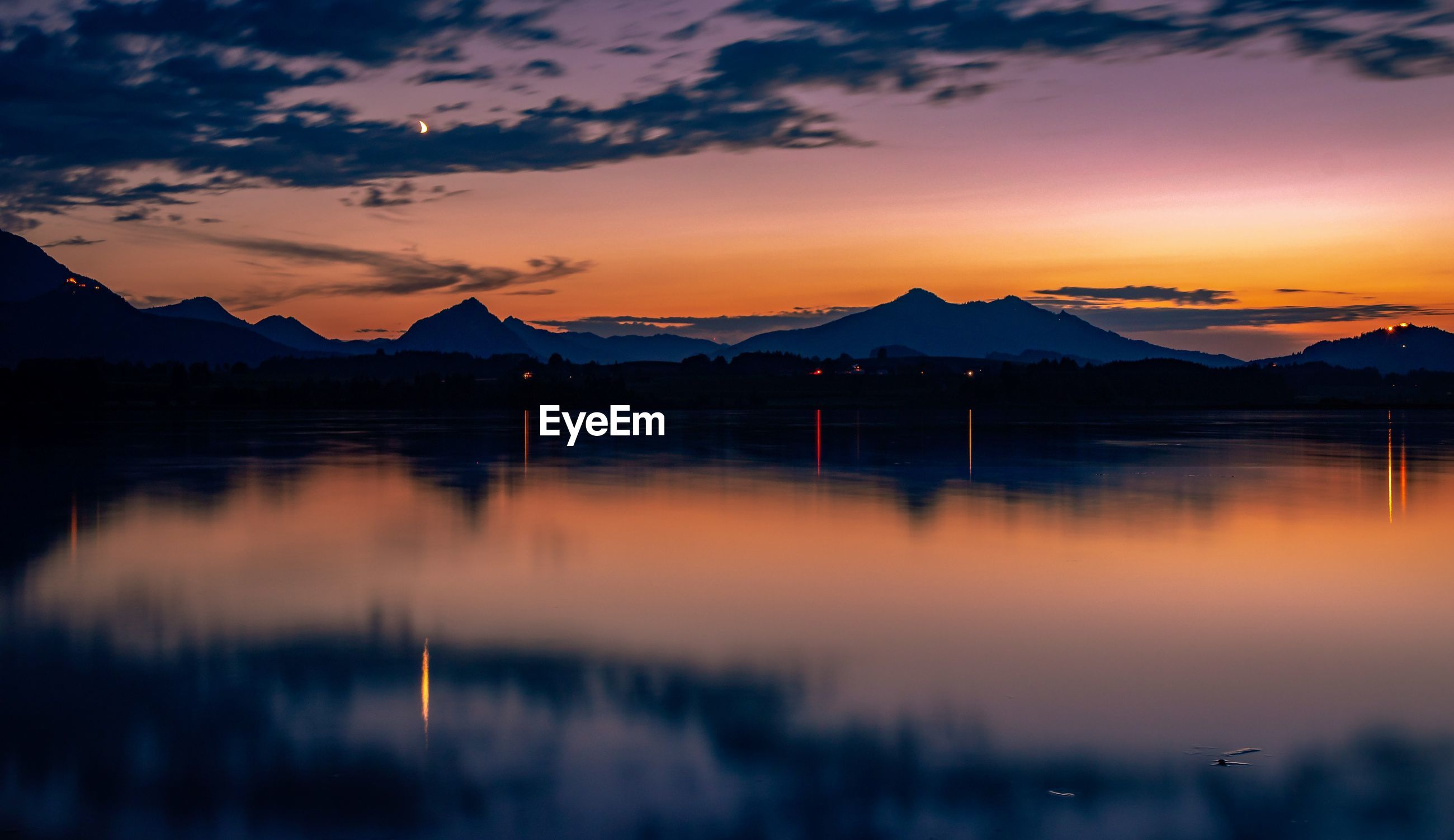 SCENIC VIEW OF LAKE BY SILHOUETTE MOUNTAIN AGAINST ORANGE SKY