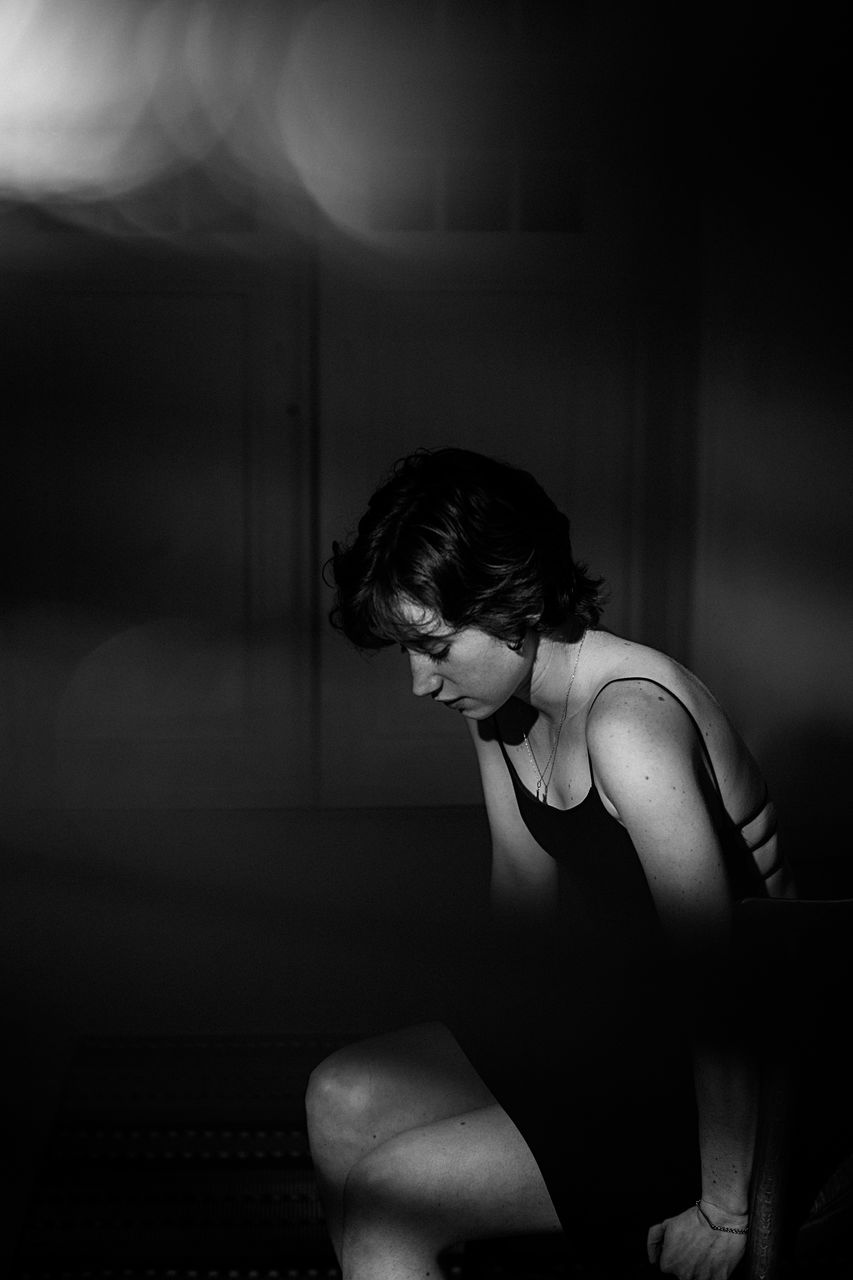 Side view of thoughtful young woman looking away while sitting in darkroom