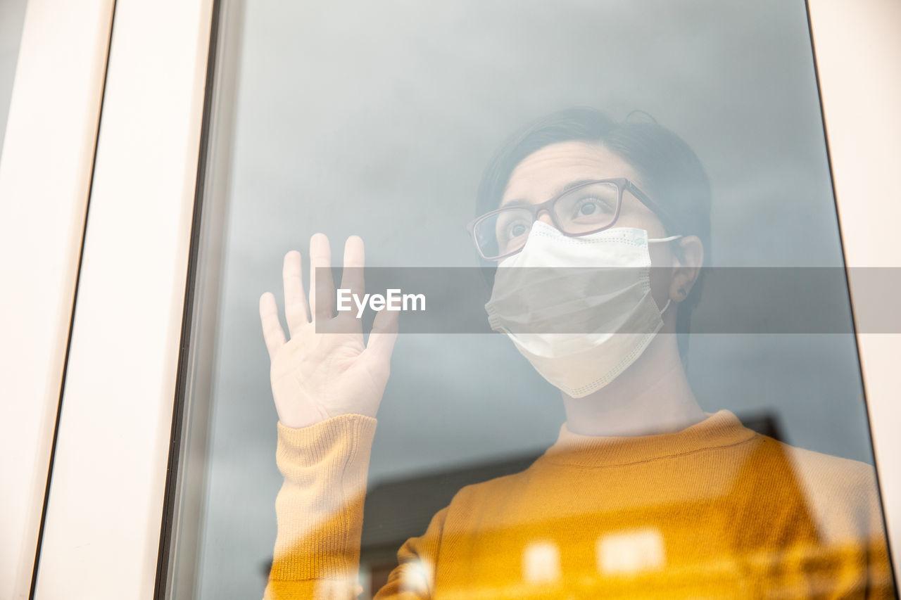 Woman wearing mask looking through window